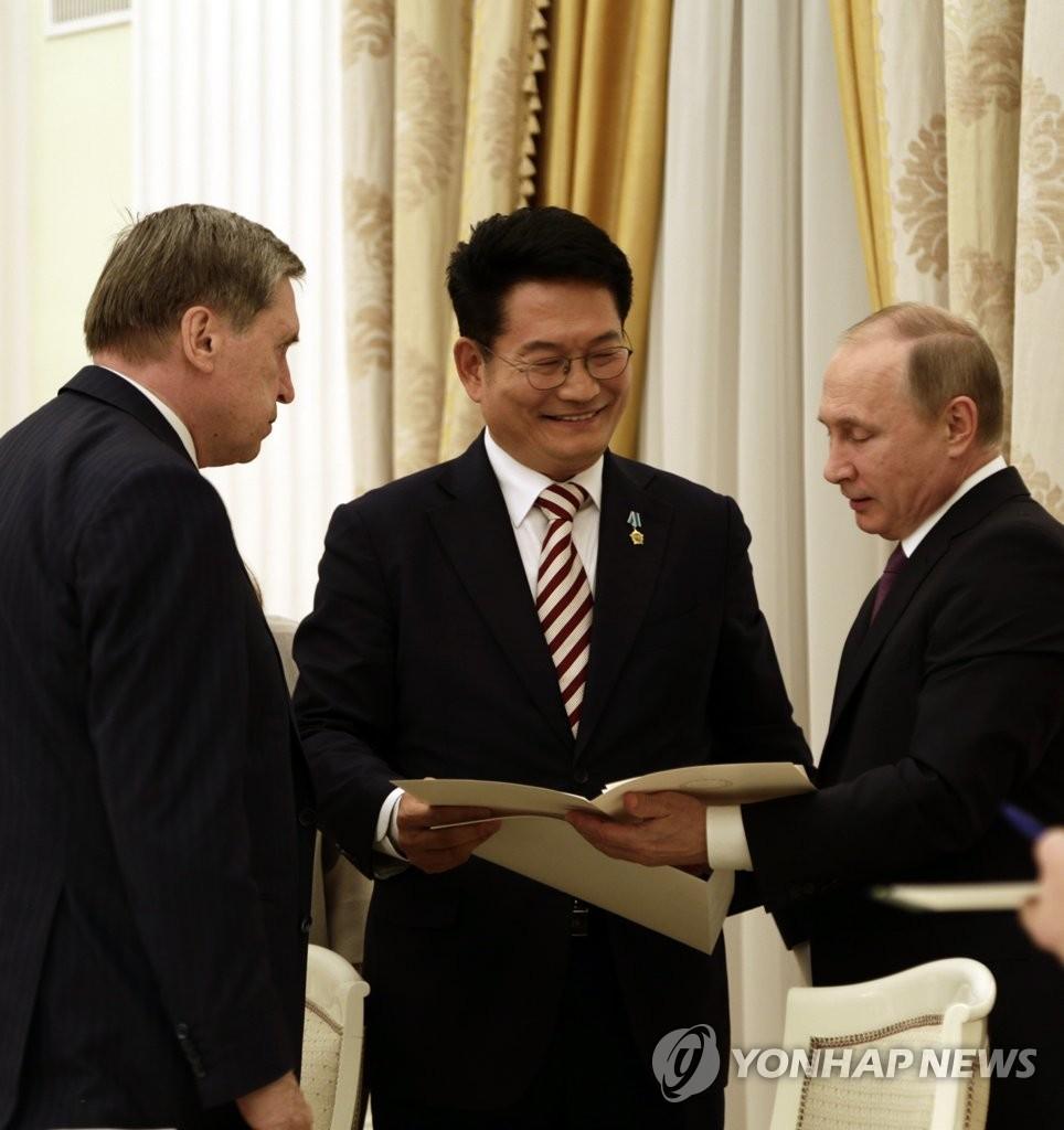 5月24日,在俄罗斯克林姆林宫,文在寅特使宋永吉(中)拜会俄罗斯总统普京,转交文在寅亲笔信。(韩联社)
