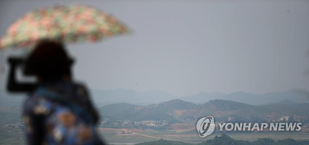 资料图片:6月1日下午,在韩国京畿道坡州乌头山统一展望台,一名游客眺望朝鲜黄海北道开丰郡。(韩联社)