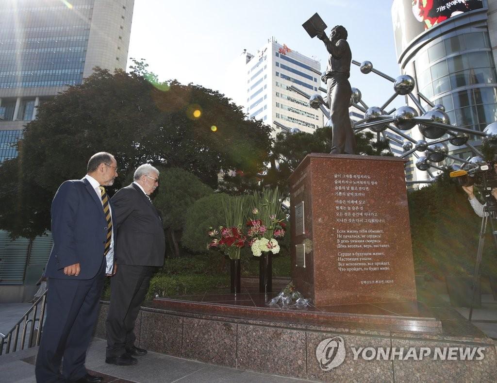 6月5日上日,塔斯社副总编辑阿布尔哈金(左)和副社长古斯曼给普希金铜像献花后,认真阅读铜像介绍。(韩联社)