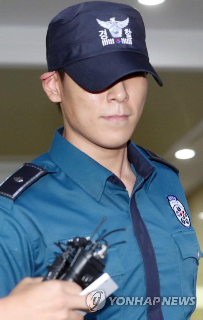 6月5日下午,在首尔江南警察署,T.O.P在警署外遭记者追问。(韩联社)