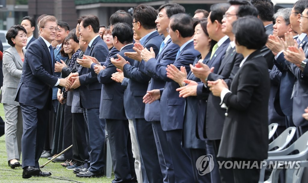 """韩国总统文在寅携夫人于6月10日出席在首尔广场举行的""""6•10民主抗争""""30周年纪念仪式,与出席会议的议员握手。(韩联社)"""