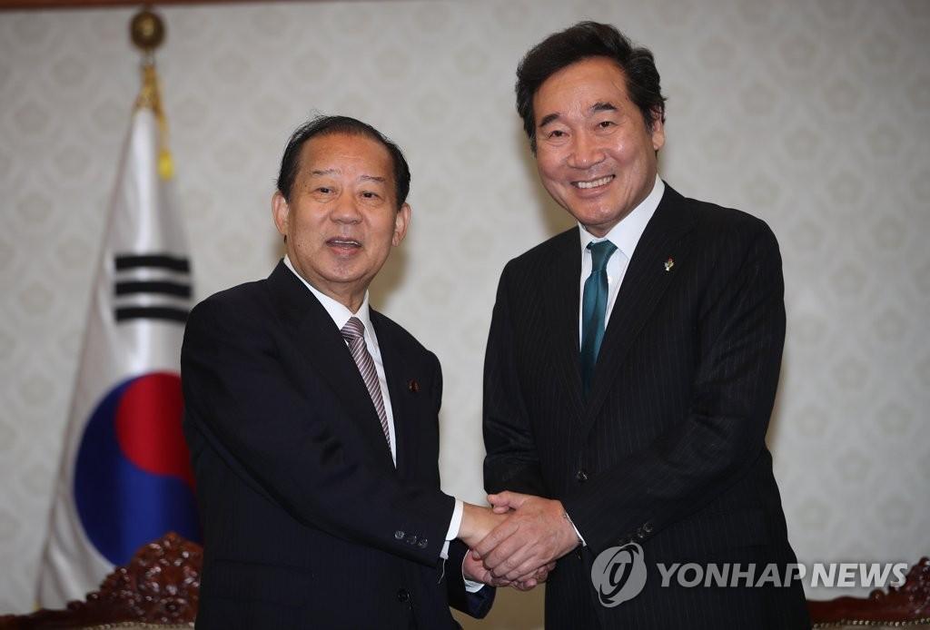 6月12日,在韩国中央政府首尔办公楼,韩国总理李洛渊与日本总理安倍晋三特使、自民党干事长二阶俊博(左)握手。(韩联社)