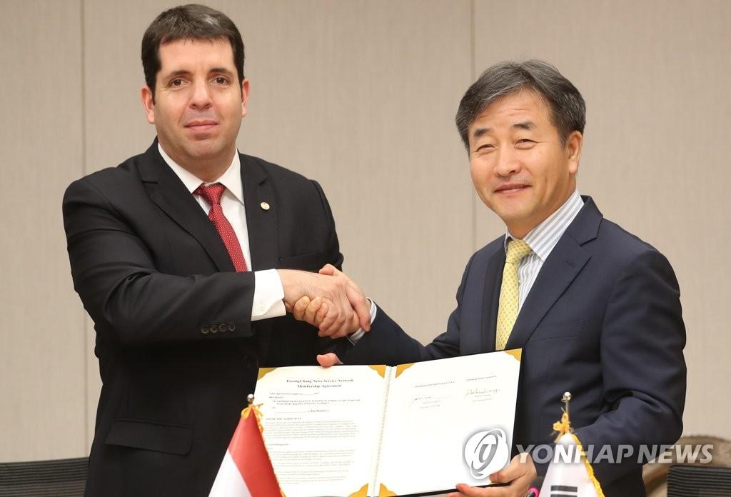 6月14日,在首尔韩联社办公楼,卡利加里(左)与朴鲁晃在签约仪式上握手合影。(韩联社)