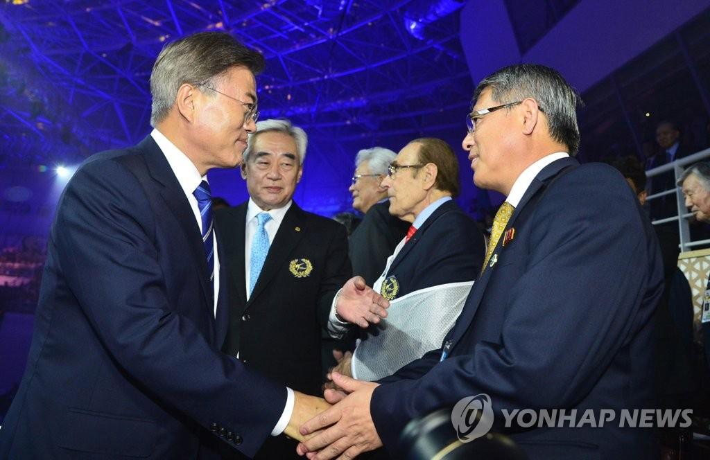 6月24日下午,在韩国全罗北道茂朱郡,总统文在寅(左)出席2017世界跆拳道锦标赛开幕式,与ITF主席李勇鲜亲切握手。(韩联社)