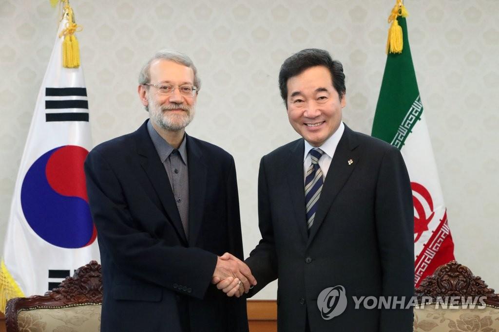 6月28日上午,在韩国中央政府首尔办公大楼,韩国国务总理李洛渊(右)与伊朗议长阿里·拉里贾尼握手合影。(韩联社)