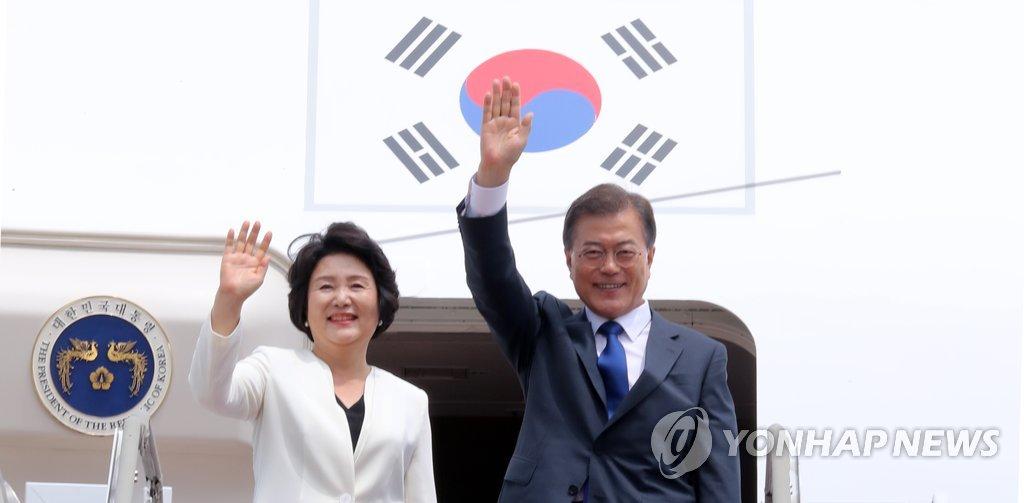 6月28日下午,韩国总统文在寅(右)与夫人金正淑女士搭乘赴美专机前向欢送人群挥手致意。(韩联社)