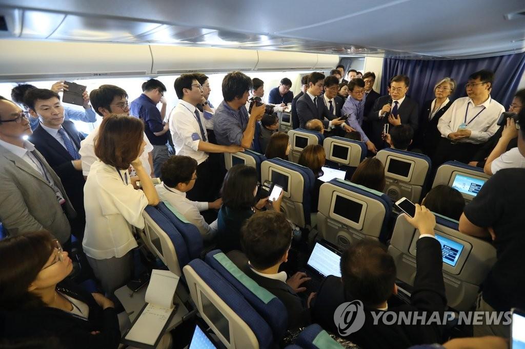6月28日下午,文在寅在专机上回答记者提问。(韩联社)