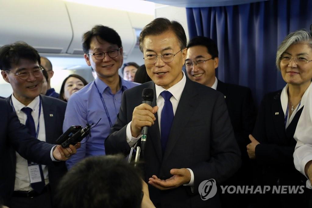 6月28日下午,韩国总统文在寅(居中,手拿麦克风)在专机上回答记者提问。(韩联社)