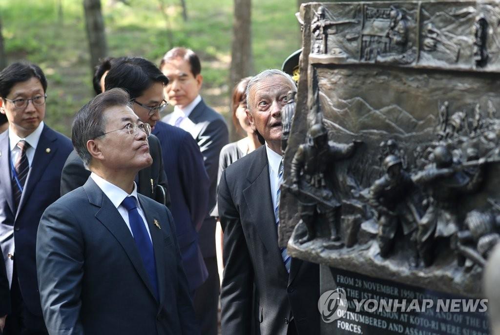 6月28日下午,在美国弗吉尼亚州的长津湖战役纪念碑,韩国总统文在寅(左)正在倾听纪念碑讲解。(韩联社)