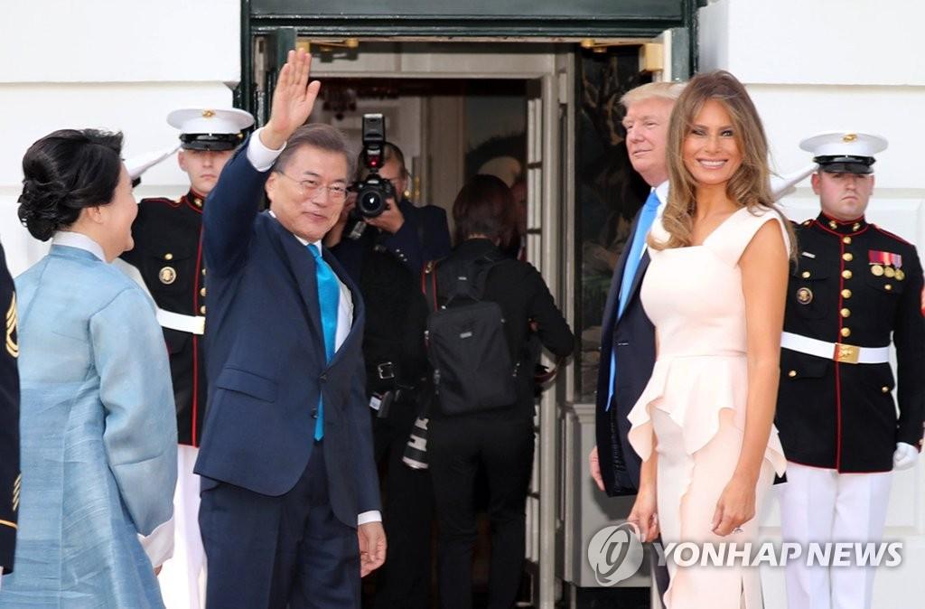当地时间6月29日下午,在美国华盛顿,韩国总统文在寅(左二)携夫人金正淑(左一)抵达白宫后向媒体记者们挥手致意。(韩联社)