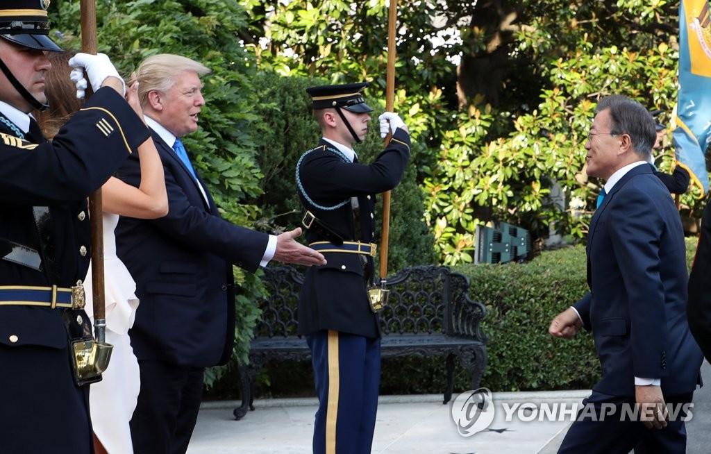 当地时间6月29日,在美国白宫,文在寅(右)与特朗普亲切寒暄。(韩联社)