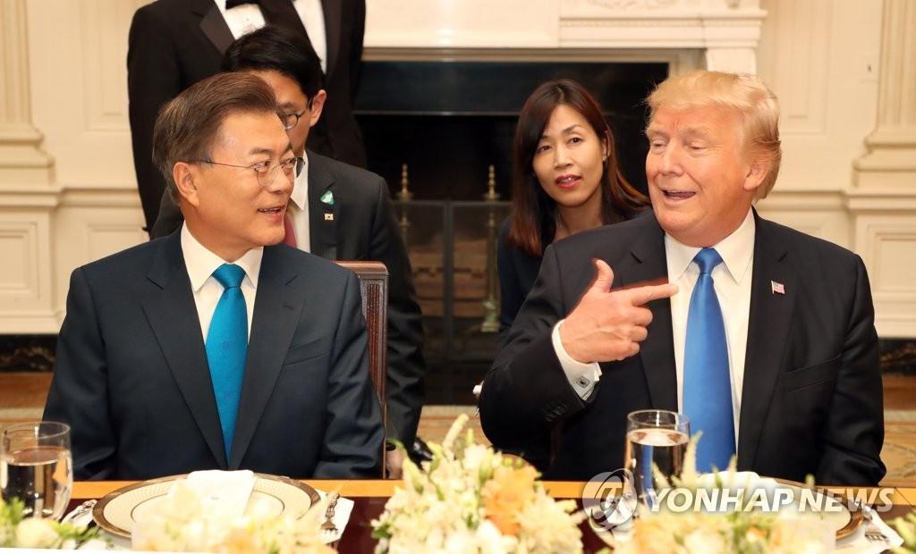 6月29日下午,在美国白宫,韩国总统文在寅(左)与美国总统特朗普在晚宴上亲切交谈。(韩联社)