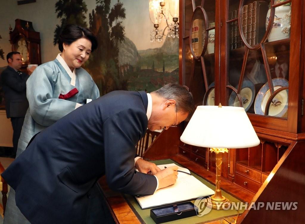 当地时间6月29日,文在寅抵达美国白宫后,在留言簿上留言。(韩联社)