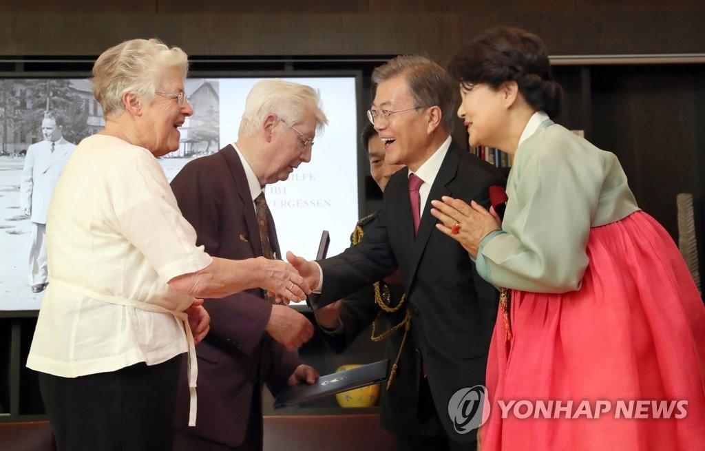 当地时间7月5日,在德国柏林,文在寅(右二)向德国医疗支援团生存者颁发勋章并亲切握手。(韩联社)