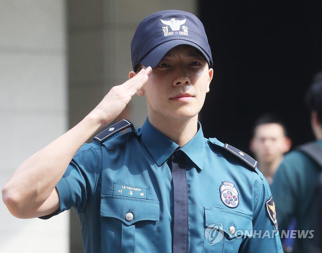 14日上午,在首尔地方警察厅,东海向前来迎接的粉丝们敬军礼。(韩联社)
