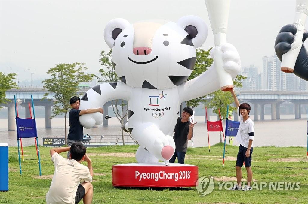 市民在与平昌冬奥会的吉祥物Soohorang雕像合影留念。(韩联社)