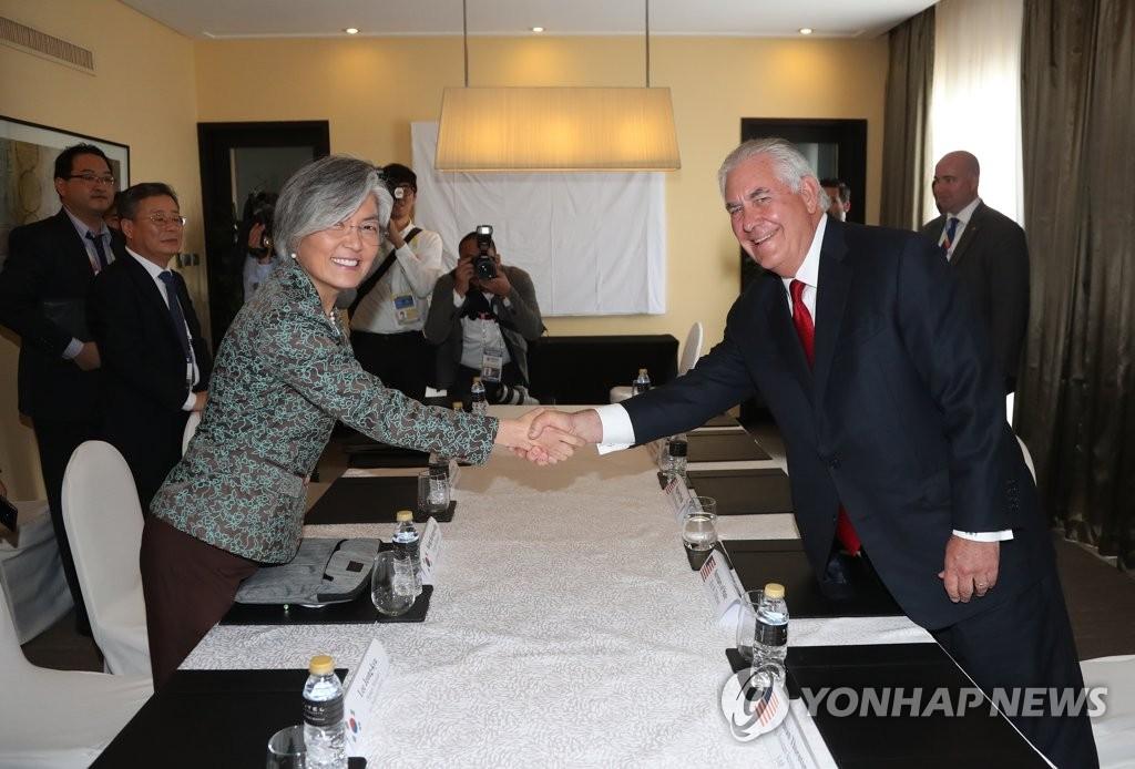 8月6日下午,在马尼拉的一家酒店,韩国外长康京和与美国国务卿蒂勒森在双边会谈上亲切握手。(韩联社)