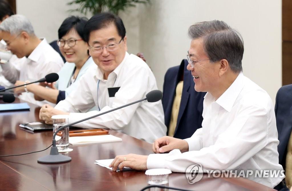 8月7日,在青瓦台的首席与辅佐官会议上,文在寅与青瓦台官员谈笑风生。(韩联社)