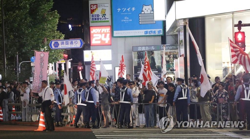 资料图片:8月12日,在东京都千代田区靖国神社前,日本右翼分子举着战犯旗辱骂妨碍捧烛游行的韩日公民团体成员。(韩联社)