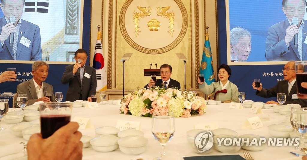 8月14日,在青瓦台,文在寅(右三)和夫人金正淑女士(右二)在午宴上举杯。(韩联社)