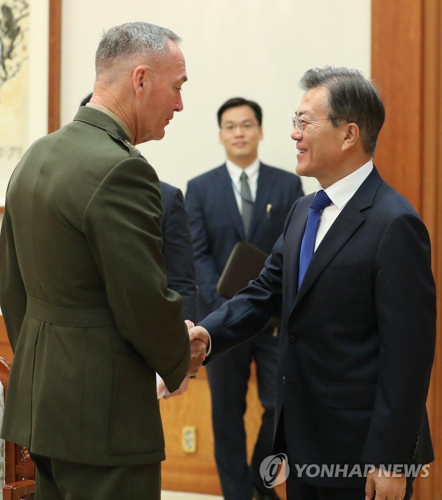 8月14日下午,在青瓦台,韩国总统文在寅(右)接见美国参谋长联席会议主席邓福德,两人亲切握手。(韩联社)