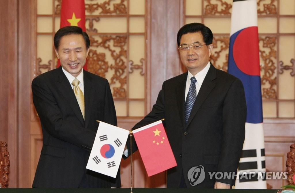 资料图片:2008年5月27日,在北京人民大会堂,韩国总统李明博(左)与中国国家主席胡锦涛握手合影。(韩联社)