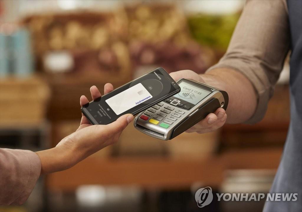 图为一名消费者利用三星智付付款。(韩联社/三星电子提供)