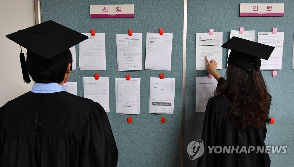 资料图片:2017年8月23日,在位于首尔钟路区的祥明大学,参加2017年度夏季毕业典礼的毕业生们正在浏览招聘信息。(韩联社)
