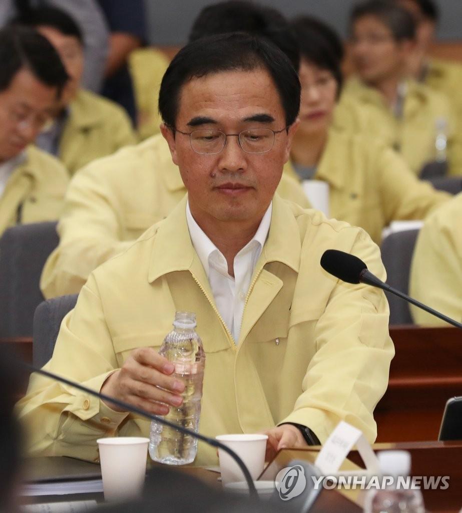 """8月23日下午,在首尔市外交部大楼的""""2017外交、统一工作核心政策讨论会"""",统一部长官赵明均在发言前喝水。(韩联社)"""