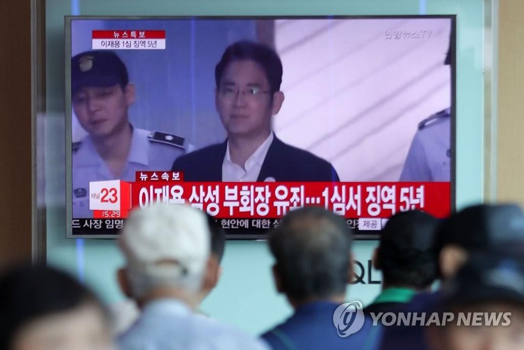 8月25日下午,在首尔站,首尔市民正在围观判决三星副会长李在镕有罪的新闻。(韩联社)