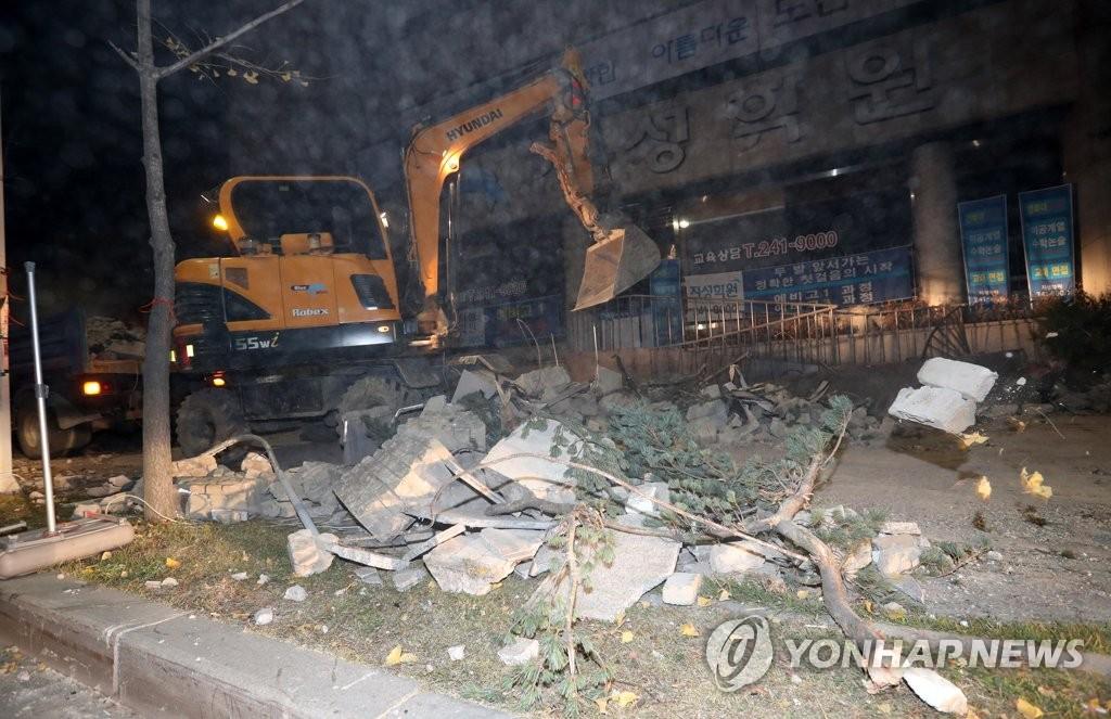 资料图片:11月15日,韩国浦项市,工作人员正在清理地震中掉落的砖瓦。(韩联社)
