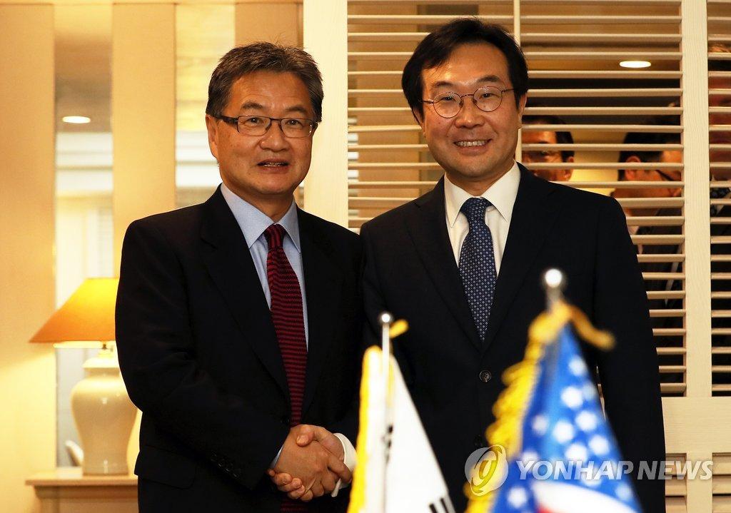11月17日,在济州西归浦市新罗酒店,李度勋(右)和约瑟夫·尹在会晤前握手合影。(韩联社)