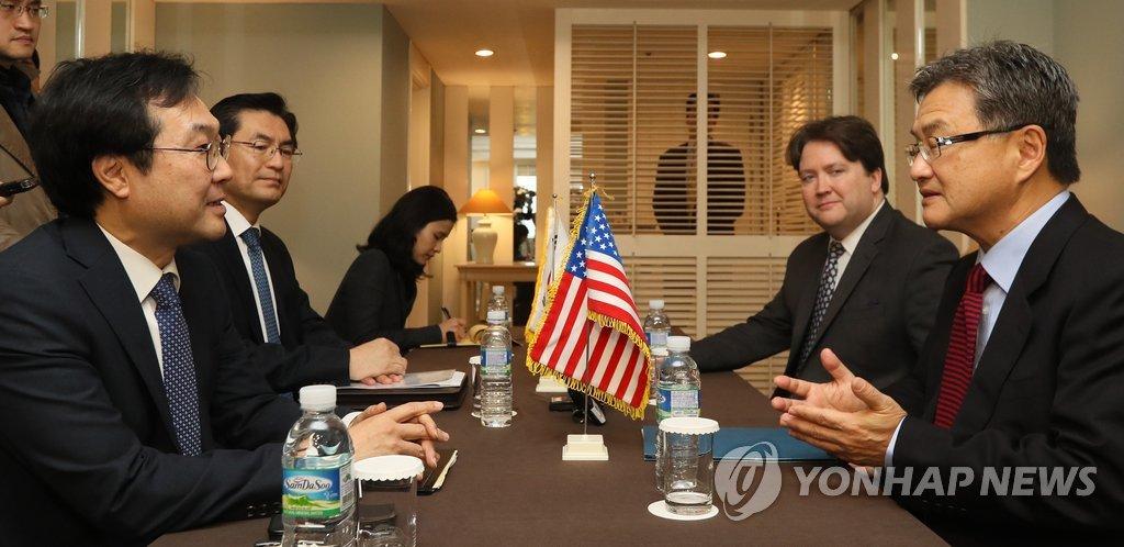 11月17日,在济州西归浦市新罗酒店,李度勋(左一)和约瑟夫·尹(右一)进行交谈。(韩联社)