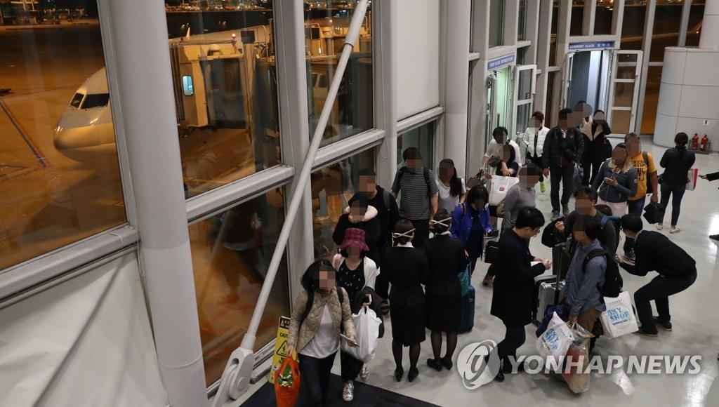 12月1日凌晨,曾滞留巴厘岛的韩国公民抵达仁川国际机场。(韩联社)