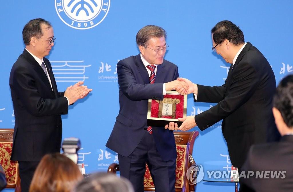 """12月15日,在北京大学,正在中国访问的韩国总统文在寅(左二)发表演讲。图为北大党委书记郝平(右)向文在寅赠送""""大学堂""""牌匾。左为北大校长林建华。(韩联社)"""