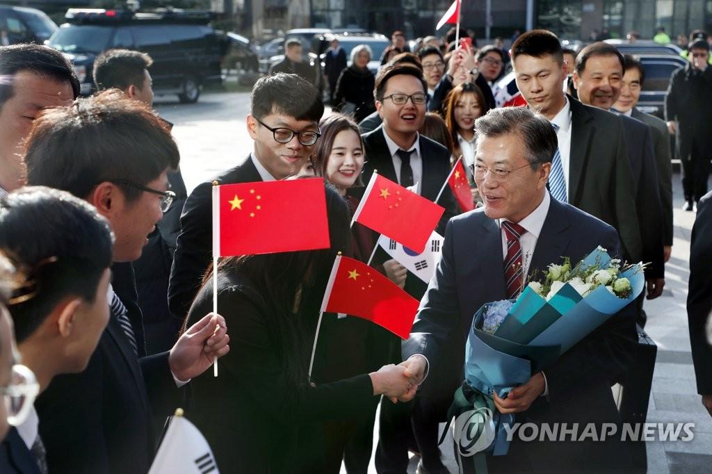 12月15日,在北京大学,正在中国访问的韩国总统文在寅发表演讲。图为文在寅受到北大学生的夹道欢迎。(韩联社)
