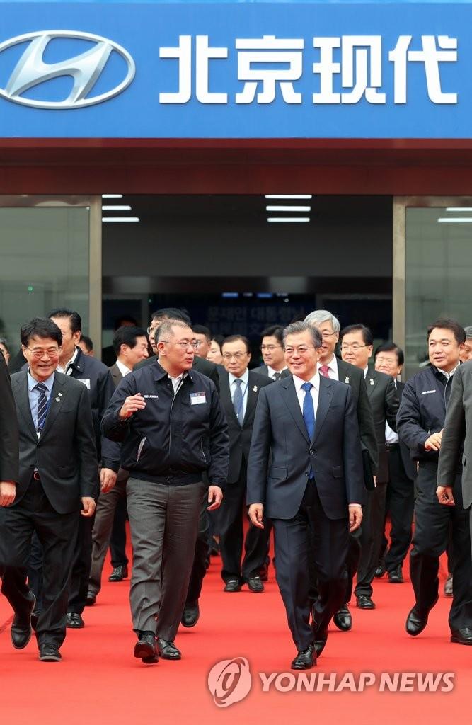 资料图片:2017年12月16日,在重庆北京现代汽车第五工厂,韩国总统文在寅(前排左三)结束参观走出工厂并与现代汽车副会长郑义宣(前排左二)交谈。韩联社