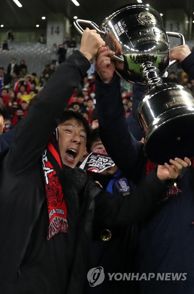 韩国男足主帅举奖杯庆祝夺冠