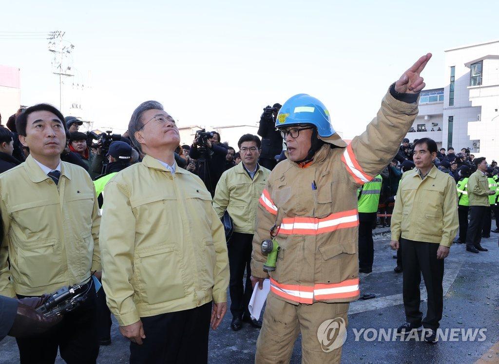 12月22日下午,在堤川火灾现场,文在寅(左二)正在听取有关情况汇报。(韩联社)