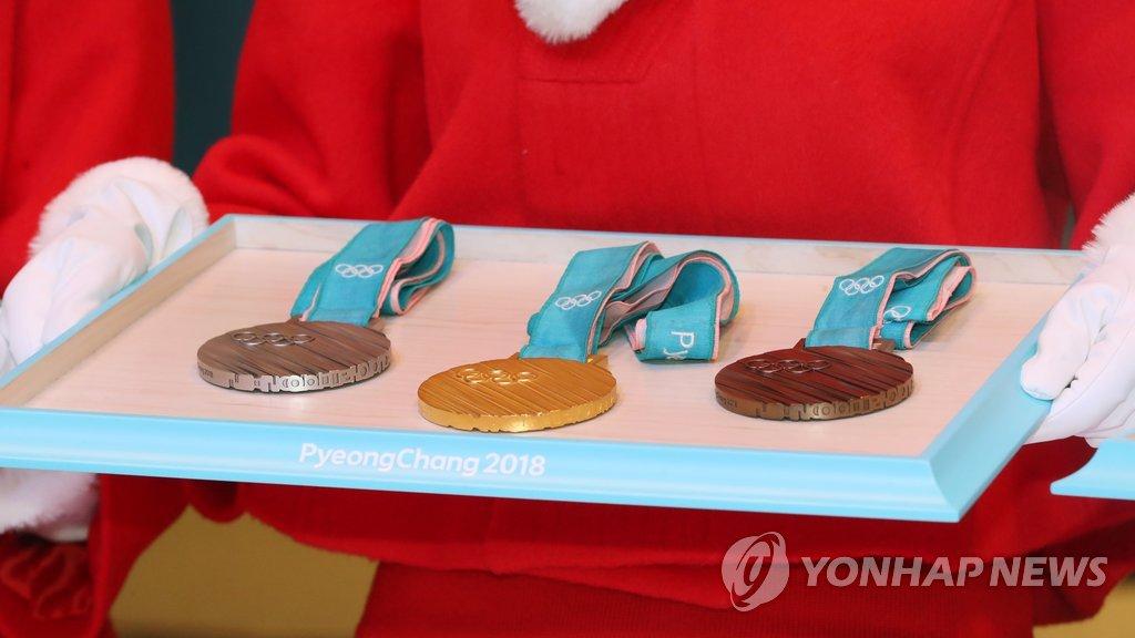 资料图片:2017年12月27日,在首尔媒体中心,工作人员在2018平昌冬奥会颁奖礼用品发布会举行上展出奖牌标准样式。韩联社