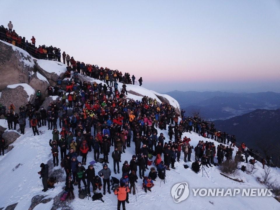 资料图片:2018年1月1日,在首尔北汉山白云台,市民们迎接新年第一轮日出。(韩联社)