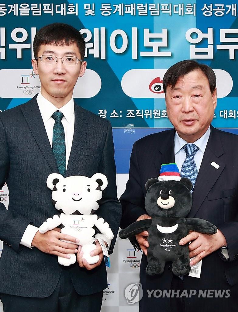 1月9日,李熙范(右)与张喆签署协议后合影留念。(韩联社/平昌冬奥组委会提供)