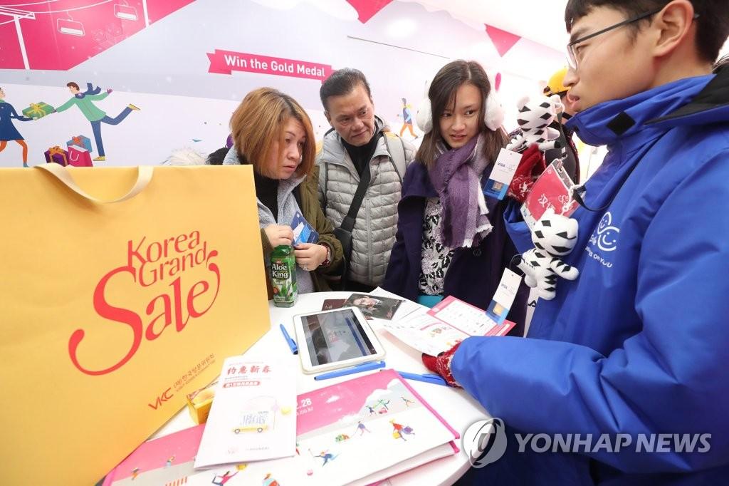 资料图片:2018韩国购物季期间,外国游客在进行咨询。(韩联社)