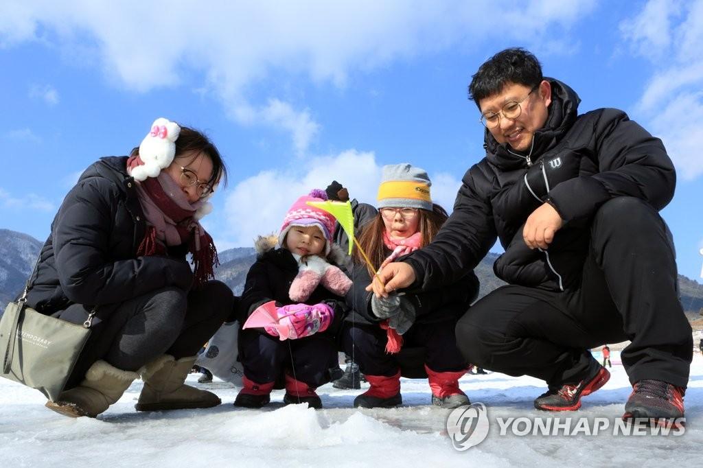 资料图片:举家出游体验冰钓。(韩联社)