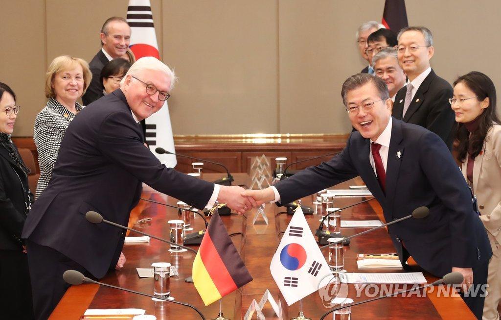2月8日上午,在韩国青瓦台,文在寅(右)和施泰因迈尔在会谈前握手合影。(韩联社)