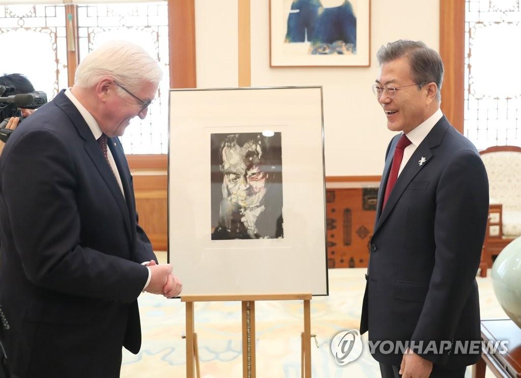 2月8日上午,在韩国青瓦台,施泰因迈尔(左)在会谈开始前向文在寅赠送了维利·勃兰特肖像画。(韩联社)