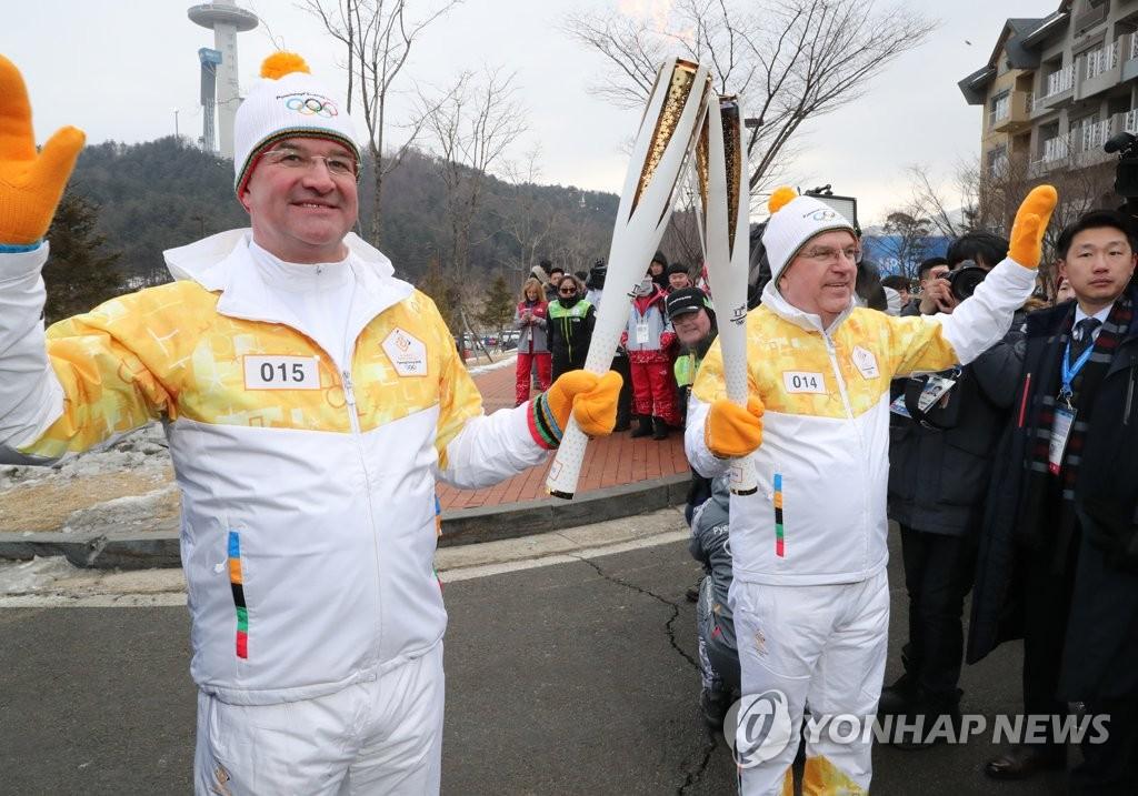 2月9日上午,在平昌阿尔卑西亚度假村附近,巴赫(右)把火炬交接给米罗斯拉夫·莱恰克。(韩联社)