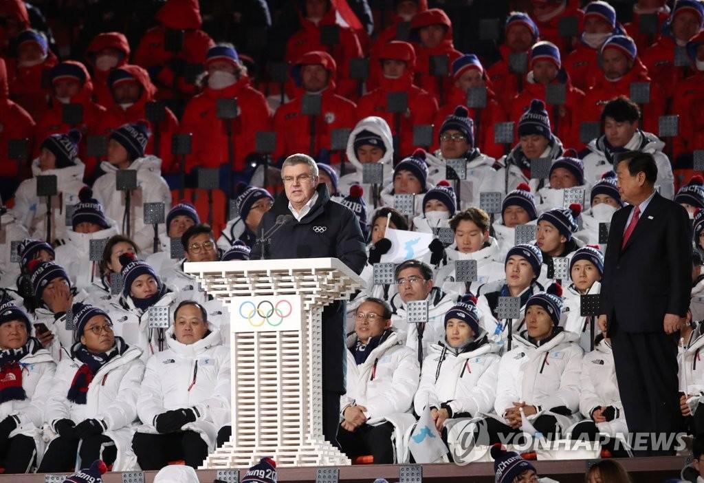 资料图片:2018年2月9日下午,在江原道平昌郡奥林匹克体育场,巴赫出席2018平昌冬奥会发表演讲。右为奥组委主席李熙范。 韩联社