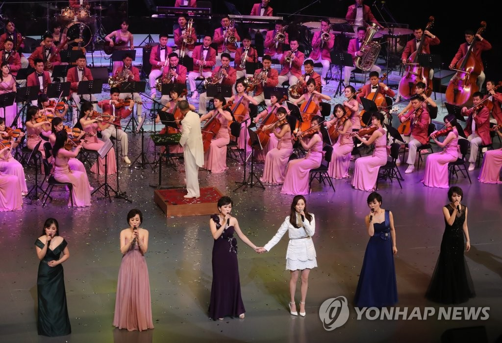 2月11日下午,在首尔国立中央剧场,少女时代成员徐贤(白衣)与乐团歌手合唱《我们的夙愿是统一》。(韩联社)