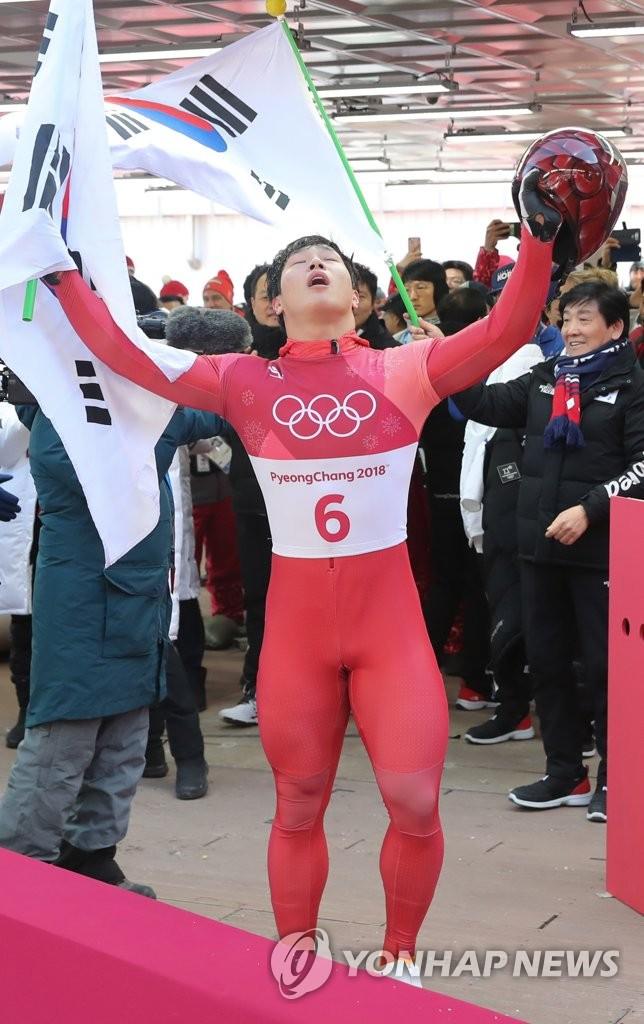 资料图片:2月16日,在平昌奥林匹克滑行中心进行的平昌冬奥会钢架雪车男子单人第四轮滑行赛上,韩国选手尹诚彬稳定发挥,成功摘金。图为尹诚彬确认成绩后高举双手欢呼。(韩联社)